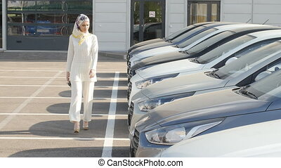 Buying or renting a car concept. Young Muslim woman chooses...
