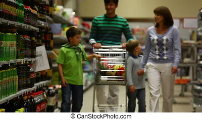 Buying products - A family of four walking along the ...