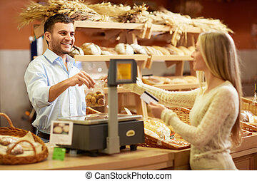 Buying - Woman with a credit card at the counter