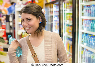 Buying Water - Young woman buying a bottle of water from a ...