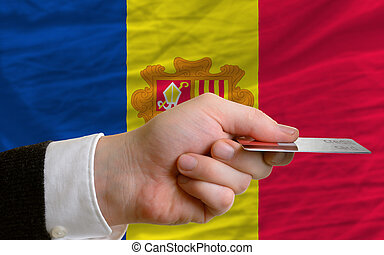 man stretching out credit card to buy goods in front of complete wavy national flag of andorra