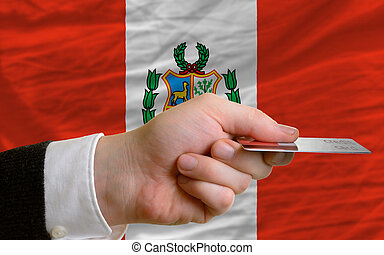 man stretching out credit card to buy goods in front of complete wavy national flag of peru