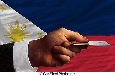 man stretching out credit card to buy goods in front of complete wavy national flag of philippines