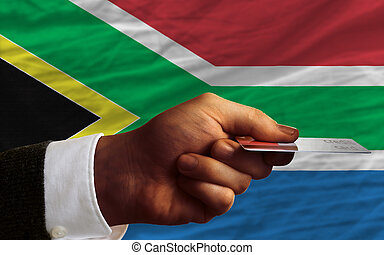 man stretching out credit card to buy goods in front of complete wavy national flag of south africa