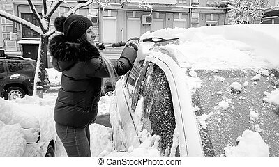 Bw closeup image of beautiful smiling lady in coat , jeans and braun hat trying to clean up snow covered car by blue brush after snow fall .