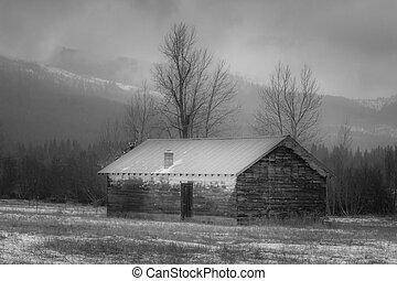 B&W of shed in snowy field.