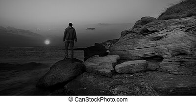 black and white sunrise seascape with alone man on the rocks