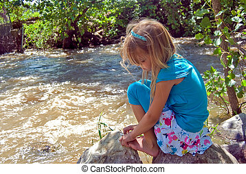 By The Brook - Little girl on a rock by a brook.