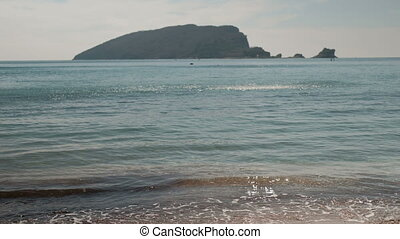 By the sea waves gently pleshutsya against the black mountain.