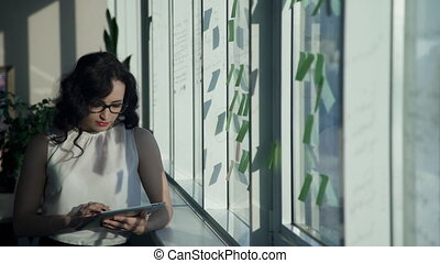 By the window stands a woman with glasses and holding a computer.