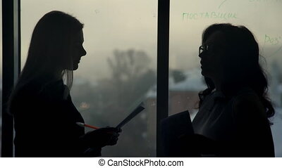 By the window there are two silhouettes of women with papers in hand.