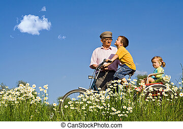 Bicycle ride with grandpa on the meadow full of daisies