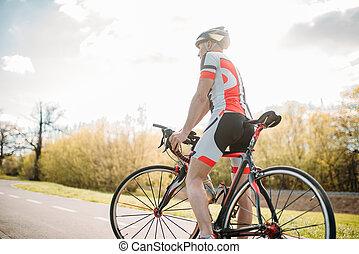 Bycyclist in helmet and sportswear on bike workout