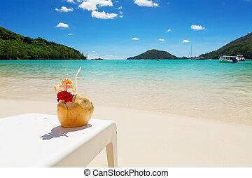 cóctel tropical, en, esqueleto coco, con, rojo, hibisco, flor, blanco, silla de la playa, con, perfecto, azul, laguna, plano de fondo
