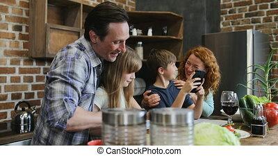 côtelette, usage, gosses, fille, nourriture famille, légumes, père, deux, ensemble, fils, téléphone portable, quoique, rire, parents, préparer, mère, intelligent, cuisine