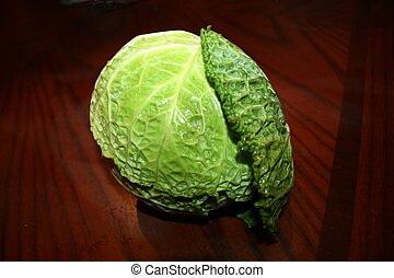 Cabbage head on brown table - Close up of green cabbage head...