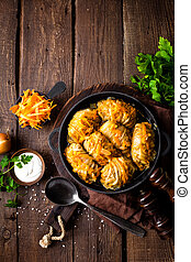 Cabbage rolls stewed with meat and vegetables in pan on dark wooden background, top view