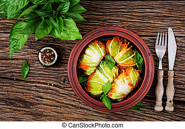 Cabbage rolls stuffed with rice with chicken fillet in tomato sauce on a wooden background. Tasty food. Top view. Flat lay