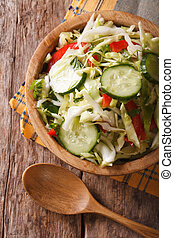 Cabbage salad with cucumbers in a bowl vertical top view