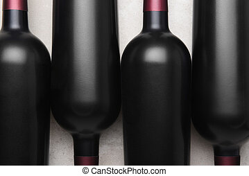 Closeup overhead shot of four red wine bottles