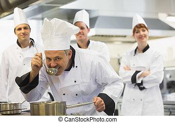 cabeza, chef, saboreo, un, sopa, y, sonriente, en cámara del juez