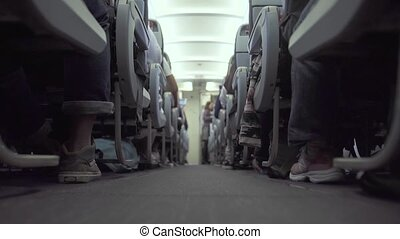 Cabin airplane with passengers sitting on seats and stewardess walking aisle in background. Passengers on seat in economy class commercial aircraft while flying. Travel concept.