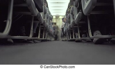 Cabin airplane with passengers sitting on seats and stewardess walking aisle while flying. Passengers on seat in economy class commercial aircraft waiting taking off. Travel concept.