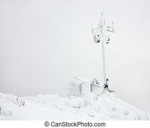 Cabin and antenna in snow.