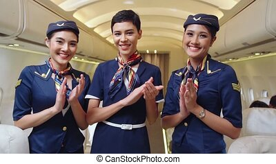 Cabin crew clapping hands in airplane . Airline transportation and tourism concept.