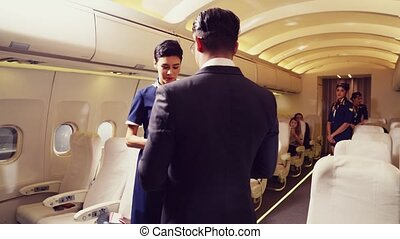 Cabin crew greeting passenger in airplane