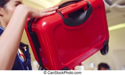 Cabin crew lift luggage bag in airplane . Airline transportation and tourism concept.