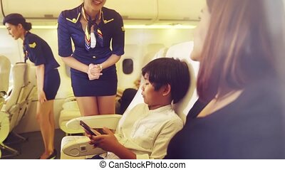 Cabin crew provide service to family in airplane . Airline ...