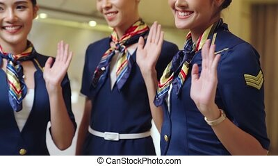 Cabin crew waving hand for greeting or goodbye . Airline transportation and tourism concept.