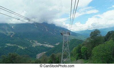 cabin of ropeway passes over mountains around Rosa Khutor...