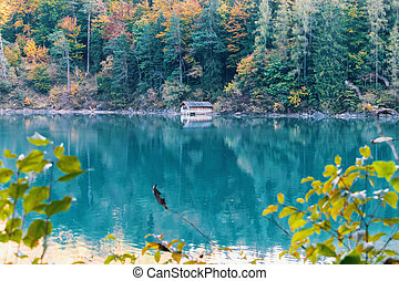 Cabin on the lake in the autumn forest in the mountains