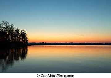 Cabin on the point reflecting in the lake with spring sunset col