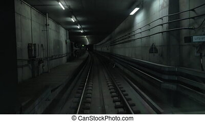 Cabin view of train moving in dark subway tunnel