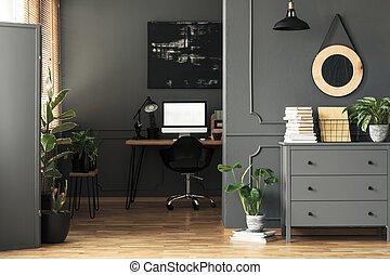 Cabinet and plants in grey workspace interior with mockup on computer desktop. Real photo