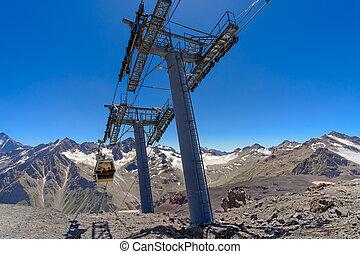 Cable car cabin over a precipice in the mountains.