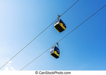 Cable car cabins liftng up on mountain against blue sky.