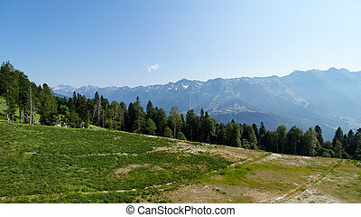 Cable car on the ski slope in a sunny summer day.