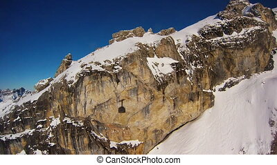 Cable car passing rock formation on big snow covered...