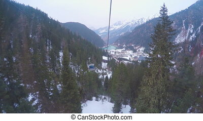 """Cable cars moving up and down cableway in mountains covered with snow, forest"""