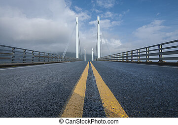 Cable stayed bridge - Dark asphalt and double yellow line on...
