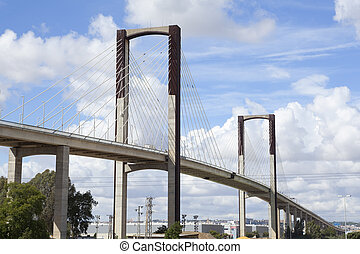 Cable-stayed bridge with traffic and clouds at background....