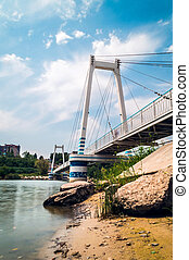 Cable-stayed suspension pedestrian bridge over the river under the blue sky with clouds