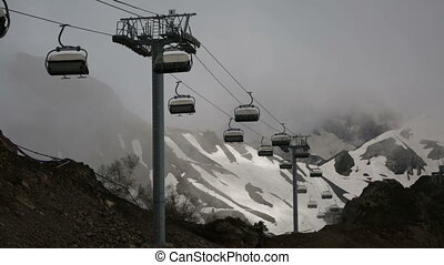Cableway with open seats in mountains in cloudy weather