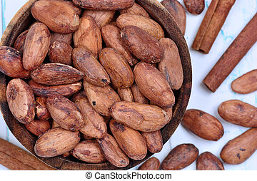 Cacao beans in a bowl with cinnamon on table
