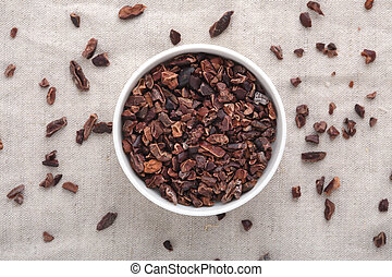 Cacao nibs in white bowl on table, top view