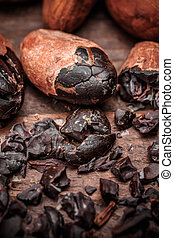 Cacao nibs with cacao beans on old wooden background